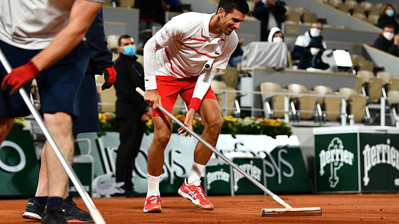 Novak Djokovic is pictured helping clean the court surface at Roland Garros during the French Open.