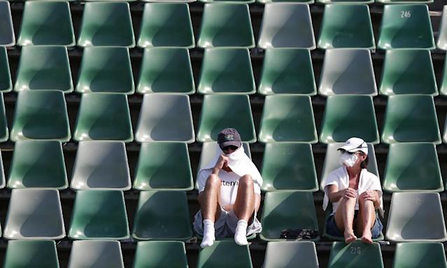 Tennis fans protect themselves from the sun during a first round match at the Australian Open tennis championship in Melbourne, Australia, Tuesday, Jan. 14, 2014