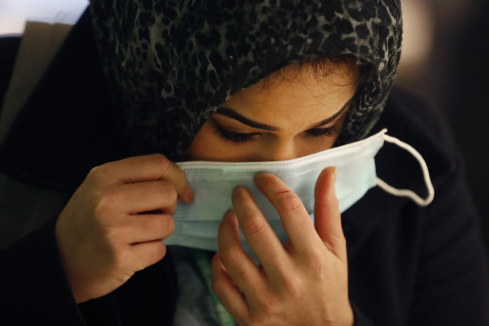 In this Wednesday, April 22, 2020, RUSH Hospital respiratory therapist Jumana Azam puts on a surgical mask after standing before a face temperature scanner as she reports for her early morning shift at the hospital in Chicago. (AP Photo/Charles Rex Arbogast)