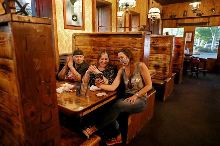 "A server sits in a booth with diners at the Silver Dollar Saloon in Marysville, Calif., on May 5. <span class=""copyright"">(Los Angeles Times)</span>"