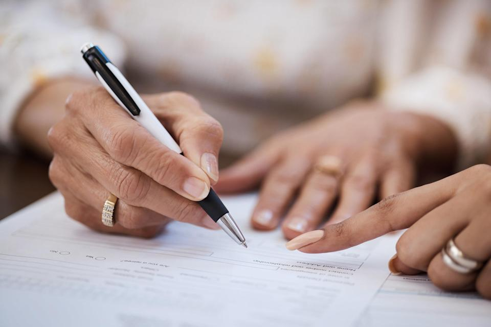 Person signing a document with a lawyer present