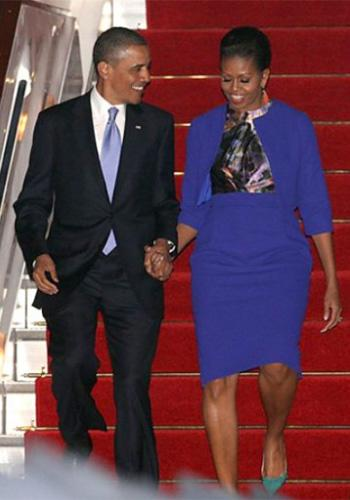 The Obamas arrive in England: Michelle Obama arrived at Stansted Airport, near London, late on Monday, May 23, wearing a royal blue pencil skirt and matching jacket with a printed blouse, all by British designers Preen by Thornton Bregazzi (her earrings were by Cathy Waterman). Photo by: AP