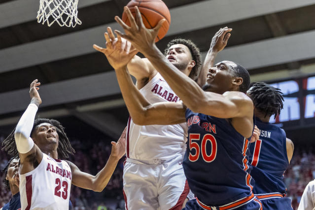 Alabama forward Alex Reese (3) and Auburn center Austin Wiley (50) chase a rebound during the first half of an NCAA college basketball game, Wednesday, Jan. 15, 2020, in Tuscaloosa, Ala. (AP Photo/Vasha Hunt)