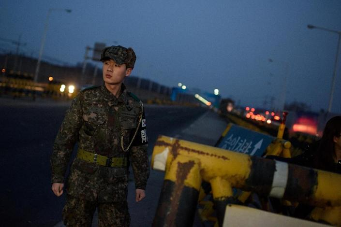 A soldier stands before a barricade at the Tongil bridge, a checkpoint leading to the Kaesong joint industrial zone, in Paju on February 11, 2016 (AFP Photo/Ed Jones)