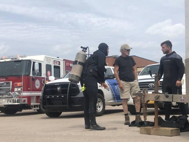 Divers arrive on the scene to help search for a man who fell into the harbour while fishing. They recovered a body about 15 minutes after beginning the search.   (Nicola MacLeod/CBC - image credit)