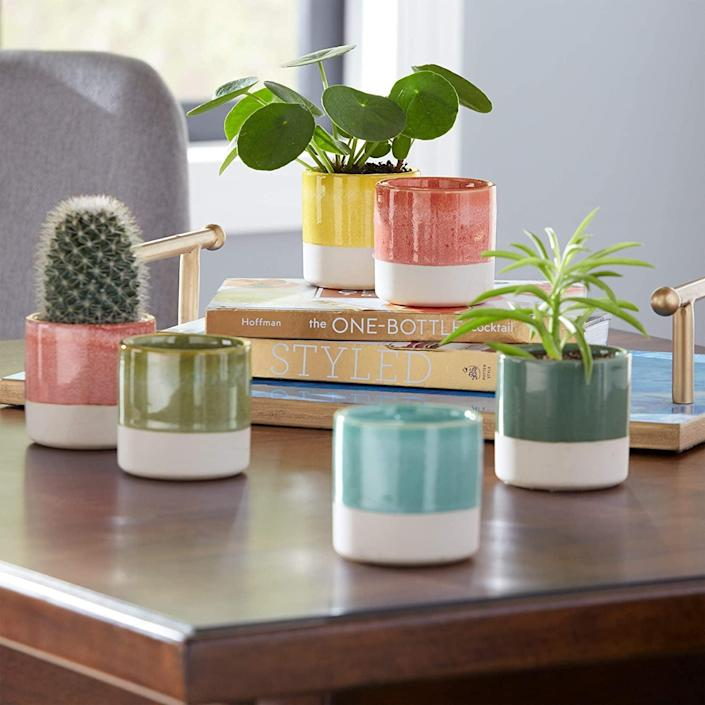 <p>Add these <span>Rivet Modern Colorful Stoneware Garden Planter Flower Pot Set</span> ($22 for six) around your space to add pops of color. You can use them on your coffee table, vanity, desk, or anywhere else that needs a boost of vibrance.</p>