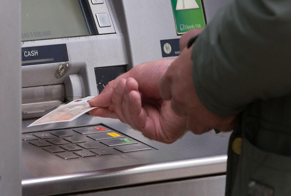 File photo dated 14/09/17 of a man withdrawing money from an ATM. The Post Office has announced a �16 million investment that will result in it owning and operating around 1,400 free-to-use cash ATMs which will be fitted with the latest technology.