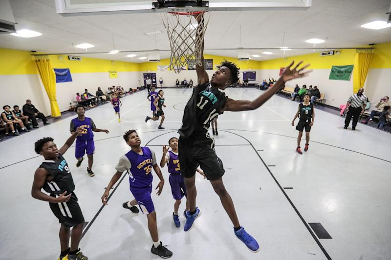 Aijalon Williams towers over other middle schoolers as he dunks during a midseason game.