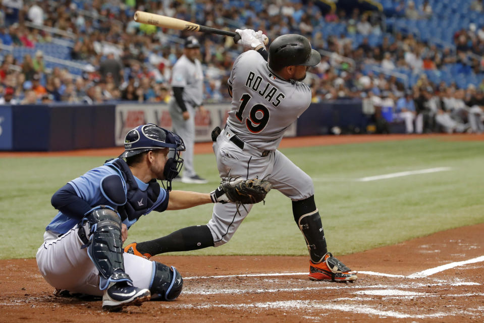 Miami Marlins' Miguel Rojas follows through on a double that knocked in three runs in front of Tampa Bay Rays catcher Adam Moore during the second inning of a baseball game Sunday, July 22, 2018, in St. Petersburg, Fla. (AP Photo/Mike Carlson)