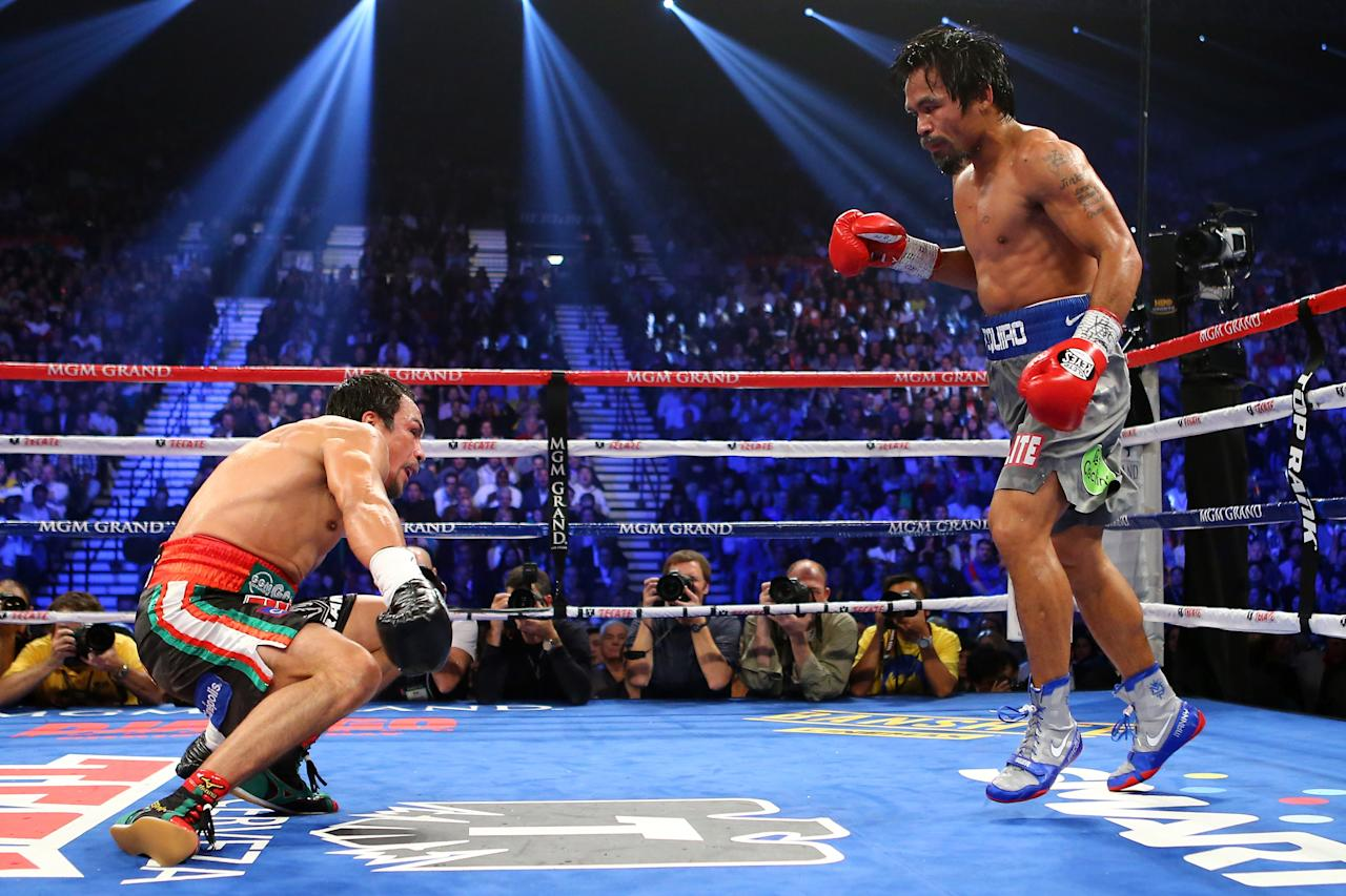 LAS VEGAS, NV - DECEMBER 08: (R-L) Manny Pacquiao knocks down Juan Manuel Marquez in the fifth round during their welterweight bout at the MGM Grand Garden Arena on December 8, 2012 in Las Vegas, Nevada. (Photo by Al Bello/Getty Images)