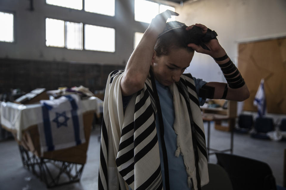 A Jewish student places his tefillin on his head during morning prayer in the synagogue of the Maoz Military Preparation Program after it was damaged by fire during overnight clashes in the mixed Jewish-Arab city of Lod, Israel, Friday, May 14, 2021. (AP Photo/Heidi Levine)