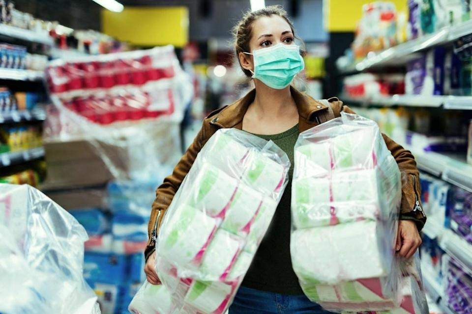 Woman wearing protective face mask while carrying packages of toilet paper and buying in time of virus pandemic.