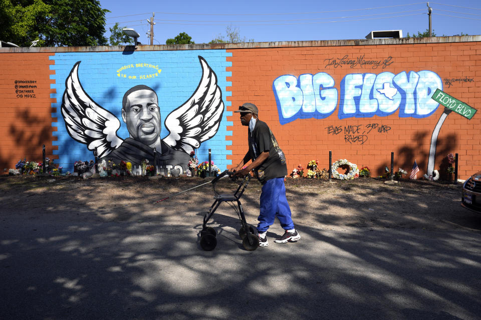 Ronaly Brooks walks past a mural in the neighborhood where George Floyd grew up Tuesday, April 20, 2021, in Houston. Former Minneapolis police Officer Derek Chauvin has been convicted of murder and manslaughter in the death of George Floyd, the explosive case that triggered worldwide protests, violence and a furious reexamination of racism and policing in the U.S. (AP Photo/David J. Phillip)
