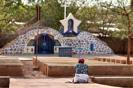 A woman prays near a statue of Virgin Mary outside the cathedral of Our Lady of Kaya in the city of Kaya, Burkina Faso May 16, 2019. REUTERS/Anne Mimault