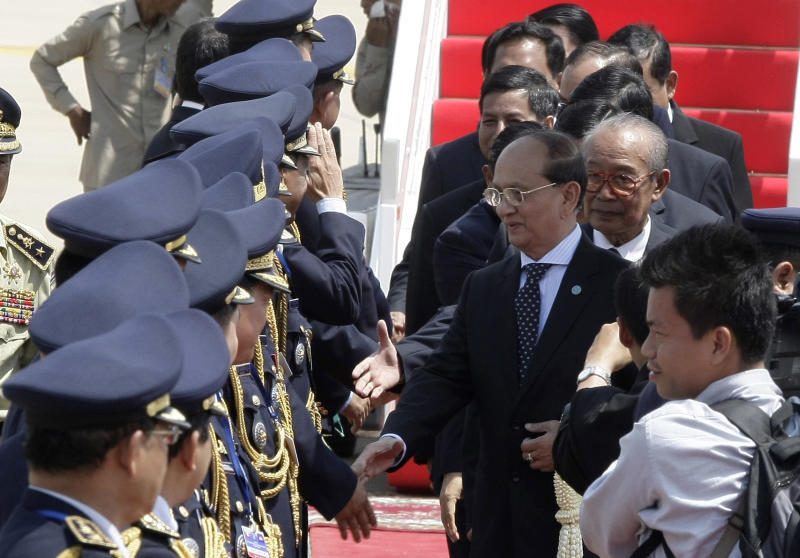 Myanmar President Thein Sein, center, greets Cambodian police officers upon his arrival at Phnom Penh International Airport in Phnom Penh, Cambodia, Wednesday, March 21, 2012. (AP Photo/Heng Sinith)