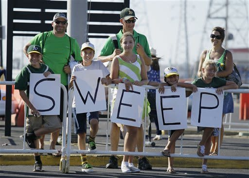 From left, Alex Gonzalez, 11, Tyler Jones, 10, Sarah Jones, 10, Gracie Gonzalez, 7, and Kylie Jones, 8, all of Biggs, Calif., hold up a sweep sign for Oakland Athletics players outside the team's parking lot following their baseball game against the New York Yankees, Sunday, July 22, 2012, in Oakland, Calif. Oakland won 5-4 to sweep their four-game series. (AP Photo/Eric Risberg)