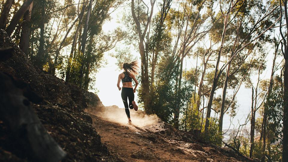 Rear view of woman trail running on a mountain path.