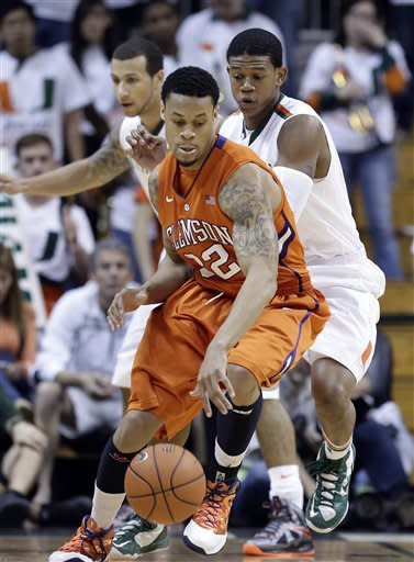 Clemson'sK.J. McDaniels (32) tries to keep the ball away from Miami's Trey McKinney Jones (4) and Rion Brown (15) during the first half of a NCAA college basketball game in Coral Gables, Fla., Saturday, March 9, 2013. (AP Photo/J Pat Carter)