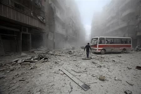 A man inspects the damage at a site hit by what activists said were barrel bombs dropped by forces loyal to Syria's President Bashar al-Assad in Aleppo's district of al-Sukari