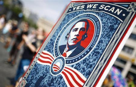 A protester holds placard showing U.S. President Obama during demonstration against NSA and in support of Snowden in Frankfurt