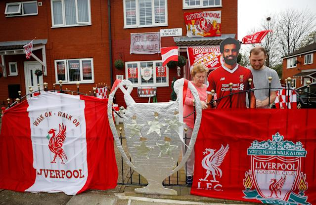 Liverpool Football Club supporters Emily and David Farley carry a cardboard cut out of Liverpool player Mo Salah outside their house which has been decorated ahead of the club's Champions League final appearance against Real Madrid, in Liverpool Britain May 9, 2018. REUTERS/Phil Noble
