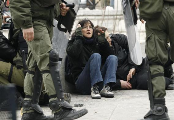 Demonstrators are detained by riot police during protests against planned reforms by Greece's coalition government in Athens, February 10, 2012.