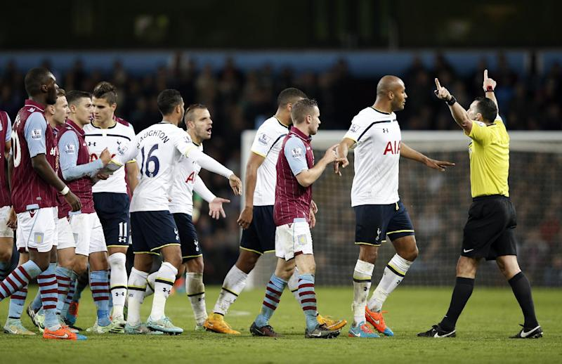 Referee Neil Swarbrick is confronted by angry Aston Villa players after Tottenham Hotspur's Belgian defender Jan Vertonghen's two footed challenge during their match in Birmingham, England, on November 2, 2014