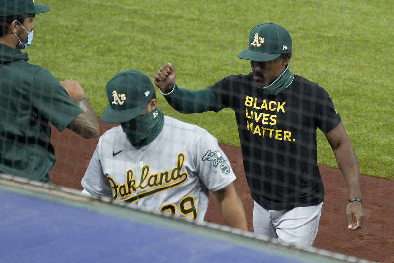 Oakland Athletics' Tony Kemp, right, wears a Black Lives Matter shirt as he greets teammates before the start a baseball game against the Texas Rangers in Arlington, Texas, Wednesday Aug. 26, 2020. (AP Photo/Tony Gutierrez)
