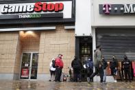 Outside a GameStop store people line up to purchase a Sony PS5 gaming console