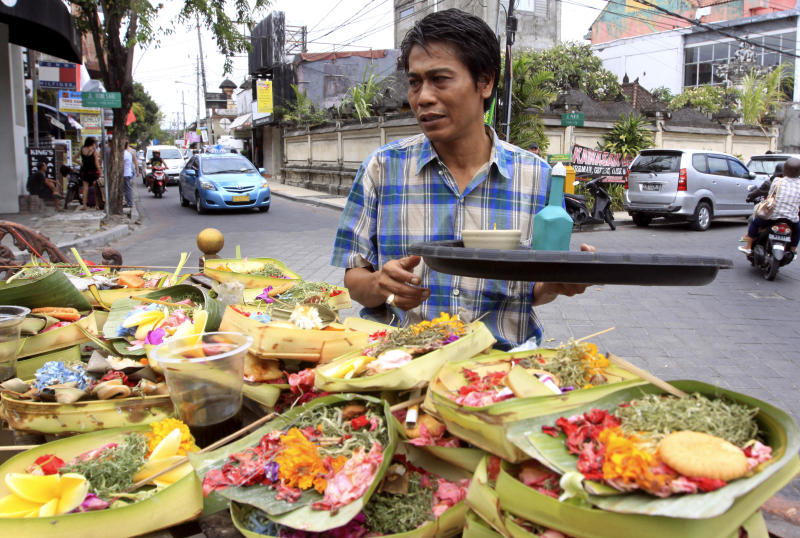 This Aug. 25, 2012 photo shows a Balinese man offering food to local god in Kuta, Bali, Indonesia. It can be hard to find Bali's serenity and beauty amid the villas with infinity pools and ads for Italian restaurants. But the rapidly developing island's simple pleasures still exist, in deserted beaches, simple meals of fried rice and coconut juice, and scenes of rural life. (AP Photo/Firdia Lisnawati)
