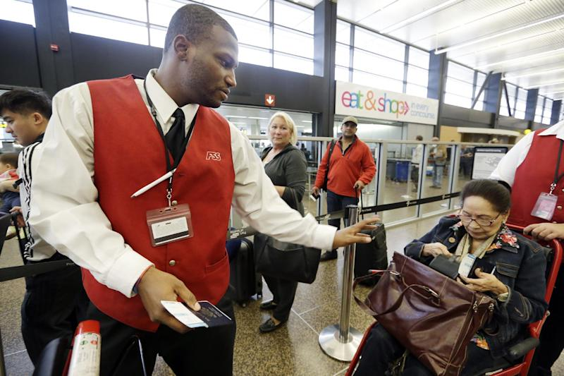 In this Tuesday, Oct. 22, 2013 photo, wheelchair attendant Erick Conley, left, assists an elderly passenger heading overseas at Seattle-Tacoma International Airport in SeaTac, Wash. There's a campaign underway to raise the minimum wage to $15 for the more than 6,300 jobs at Seattle's largest airport. If approved by voters on Nov. 5, the wage rate, as well as sick days and other benefits, would only apply to the city of SeaTac. The vote is one of the latest flashpoints in the national debate over the minimum wage after fast food workers and others held a series of summertime rallies to bring attention to their struggle to earn a living. (AP Photo/Elaine Thompson)
