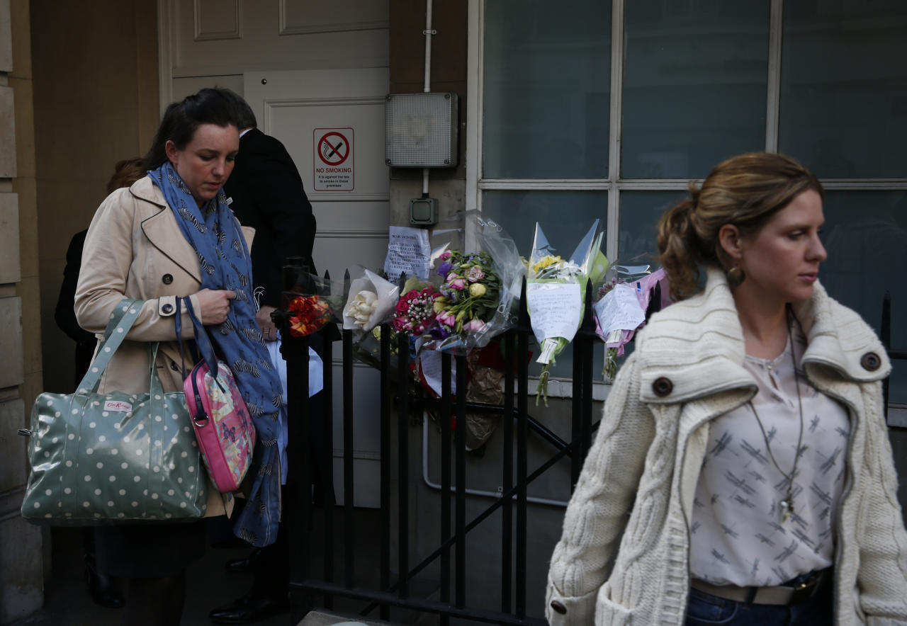 Members of King Edward VII hospital staff walk past flower tributes to late nurse Jacintha Saldanha, as they leave the residential apartments of the hospital where she was found dead, in central London, Monday, Dec. 10, 2012. Australian radio hosts managed to impersonate Queen Elizabeth II and Prince Charles and received confidential information about the Duchess of Cambridge's medical condition, in a hoax phone call to the hospital where the pregnant Duchess was staying and which was broadcast on-air. The controversial prank took a dark twist three days later with the death of nurse Saldanha, a 46-year-old mother of two, who was duped by the DJs despite their Australian accents. (AP Photo/Lefteris Pitarakis)