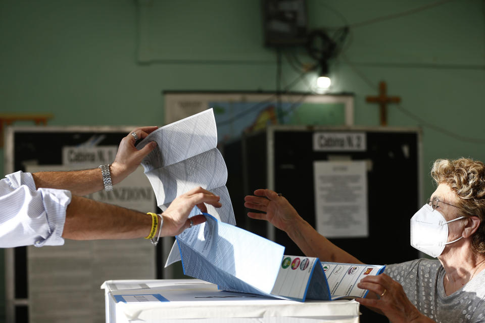 A woman receives her ballot at a polling station, in Rome, Sunday, Oct. 3, 2021. Millions of people in Italy started voting Sunday for new mayors, including in Rome and Milan, in an election widely seen as a test of political alliances before nationwide balloting just over a year away. (Cecilia Fabiano/LaPresse via AP)
