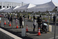 FILE - In this Jan. 7, 2021, file photo, people line up at a COVID-19 walk-up testing site on the Martin Luther King Jr. Medical Campus in Los Angeles. Coronavirus deaths and cases per day in the U.S. dropped markedly over the past couple of weeks but are still running at alarmingly high levels, and the effort to snuff out COVID-19 is becoming an ever more urgent race between the vaccine and the mutating virus. (AP Photo/Marcio Jose Sanchez, File)