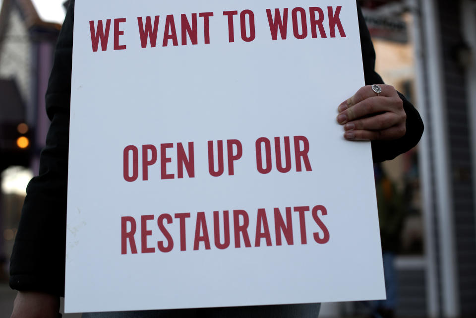 A Summit County service industry worker holds a sign while protesting the prohibition of in-person dining at restaurants Monday, Nov. 23, 2020 in Breckenridge, Colo. (Jason Connolly/Summit Daily News via AP)