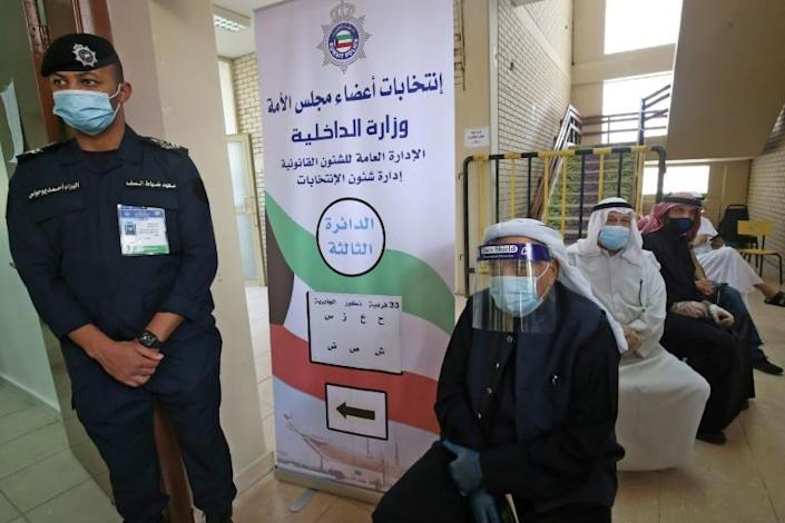 Kuwaiti men wearing protective face masks wait to cast their votes in a parliamentary election overshadowed by Covid-19