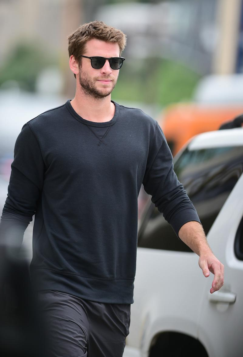 A photo of Liam Hemsworth wearing a black long-sleeve shirt, black jeans and sunglasses.