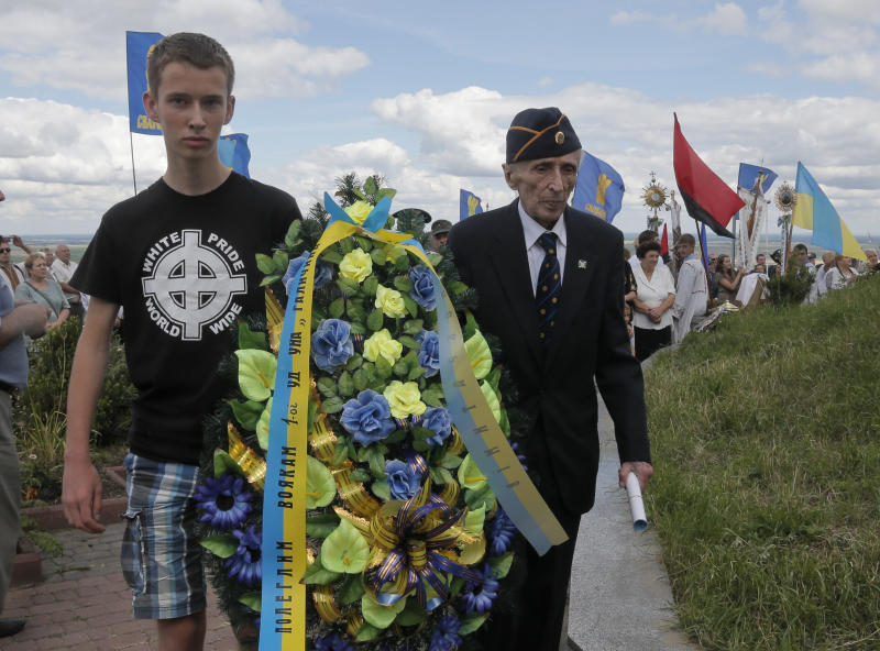 """Yevhen Kutsik, 86, former soldier of SS Galician Division, right, and a young Ukrainian nationalist wearing a T-shirt emblazoned with the neo-Nazi slogan """"white pride worldwide"""" lay a wreath to a monument to SS Galician Division near the village of Yaseniv in western Ukraine on Sunday, July 21, 2013. Western Ukraine marked the 70th anniversary of creation of the SS Galician aDivision. Writing on the wreath ribbon reads: """"To the killed soldiers of the Galician Division."""" (AP Photo/Efrem Lukatsky)"""