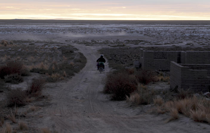 A resident drives his motorcycle on a dirt path alongside the salt-crusted former shoreline of Lake Poopo, in Punaca, Bolivia, Sunday, May 23, 2021. For many generations, the homeland of the Uru wasn't land at all: It was the brackish waters of Lake Poopo. Now what was Bolivia's second-largest lake is gone. It dried up about five years ago, victim of shrinking glaciers, water diversions for farming and contamination. (AP Photo/Juan Karita)