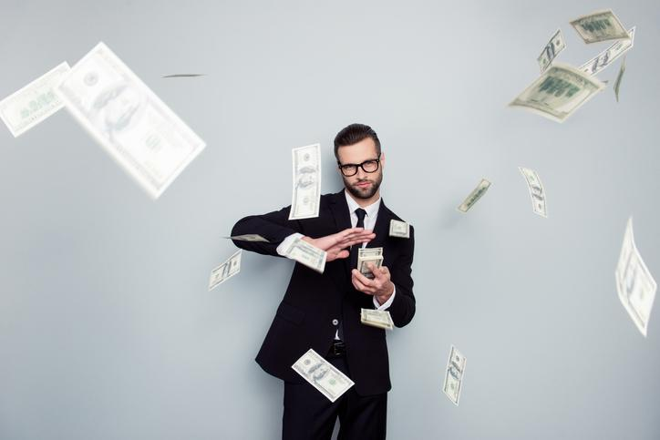 A man in a suit tossing $100 bills into the air.