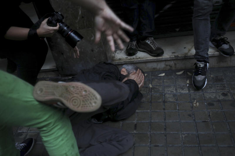 A protester falls on the ground after being hit in the face by a rubber bullet shot by Spanish National Police near the Ramon Llull school. AP Photo/Manu Brabo)