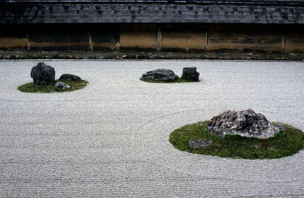 <p>The tranquil rock garden apart of Ryōan-ji Zen Buddhist Temple is touted as one of the finest examples of the Japanese dry landscape (kare-sansui). The Zen garden features large rock formations placed among carefully raked smooth pebbles; the larger stones are positioned in a way that makes them almost impossible to view all of them at the same time when seated. According to ancient lore, anyone who can see each stone from a seated position has attained complete enlightenment.</p>
