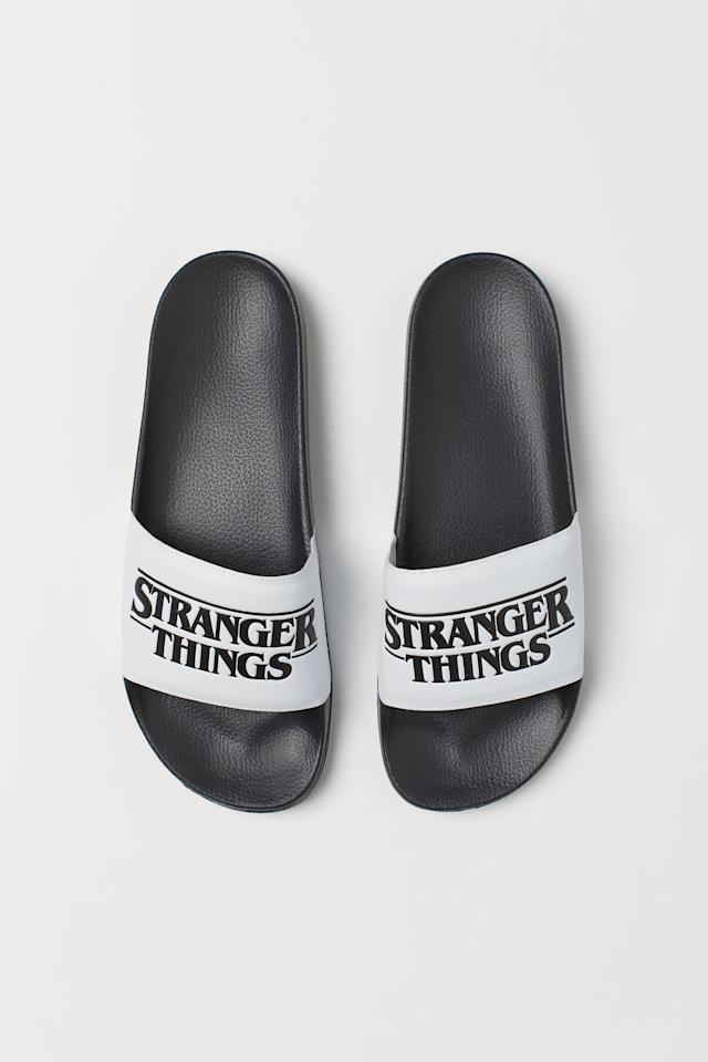 """<p><strong>H&M</strong></p><p>hm.com</p><p><strong>$7.99</strong></p><p><a href=""""https://go.redirectingat.com?id=74968X1596630&url=https%3A%2F%2Fwww2.hm.com%2Fen_us%2Fproductpage.0777008001.html&sref=http%3A%2F%2Fwww.seventeen.com%2Fcelebrity%2Fmovies-tv%2Fg23867870%2Fstranger-things-gifts-merchandise%2F"""" target=""""_blank"""">Shop Now</a></p><p>Slide your toes into these <em>Stranger Things </em>logo sandals after a long day at Hawkins Pool.<em></em></p>"""