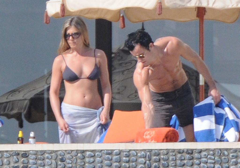 December 31, 2012: Jennifer Aniston and Justin Theroux bask in the sun while reading by the pool with friends after Justin went for an off road four-wheeler ride in Cabo San Lucas, Mexcio.