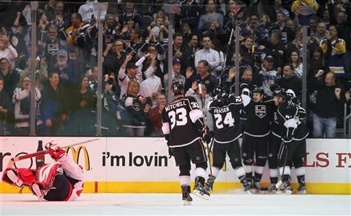 Members of the Los Angeles Kings celebrate a goal by Kyle Clifford past Washington Capitals' Tomas Vokoun during the first period of an NHL hockey game in Los Angeles, Monday, Jan. 9, 2012. (AP Photo/Chris Carlson)