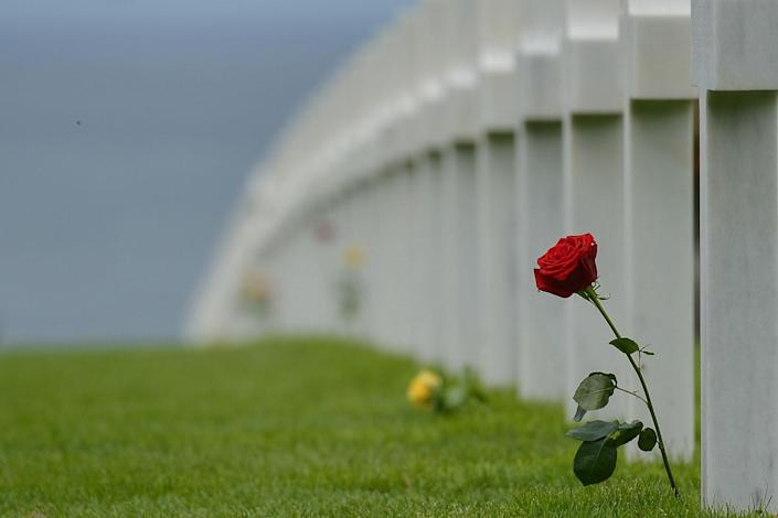 <p>A red rose left by visitors at the graves of fallen soldiers at the Normandy American Cemetery, which contains the remains of 9,387 American military dead, most killed during the invasion of Normandy and ensuing military operations in World War II. (Photo: Artur Widak/NurPhoto via Getty Images) </p>