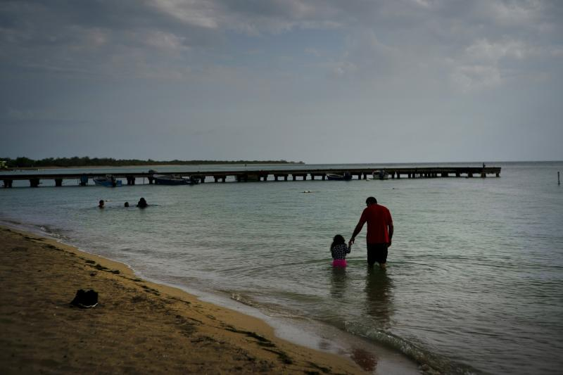 Eduardo Torres, from Puerto Rico, walks with his daughter in the ocean before the arrival of Tropical Storm Dorian in Combate, Puerto Rico, Aug. 27, 2019. (Photo: Ramon Espinosa/AP)
