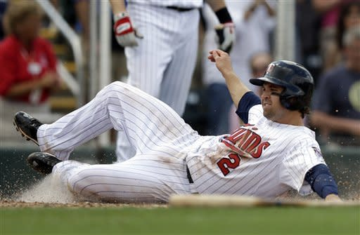 Minnesota Twins' Brian Dozier slides into the plate to score on a double by Joe Mauer in the fourth inning of an exhibition spring training baseball game against the Toronto Blue Jays in Fort Myers, Fla., Sunday March 24, 2013. (AP Photo/Elise Amendola)