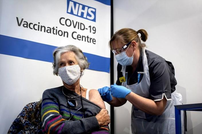Dr Doreen Brown, 85, receives the first of two Pfizer/BioNTech COVID-19 vaccine jabs administered at Guy's Hospital in London, Tuesday, Dec. 8, 2020. U.K. health authorities rolled out the first doses of a widely tested and independently reviewed COVID-19 vaccine Tuesday, starting a global immunization program that is expected to gain momentum as more serums win approval. (Victoria Jones/Pool via AP)