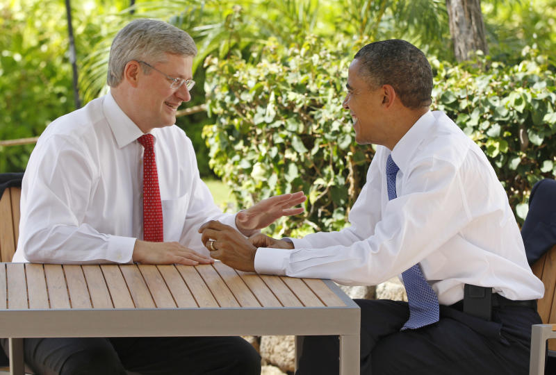 FILE - In this Nov. 13, 2011, file photo, Canadian Prime Minister Stephen Harper, left, talks with U.S. President Barack Obama following the first plenary session of the Asia-Pacific Economic Cooperation summit in Kapolei, Hawaii. Obama is convening a summit with leaders from Mexico and Canada on Monday, April 2, 2012, that aims to boost a fragile recovery and grapple with thorny energy issues against a backdrop of painfully high gas prices. The session at the White House is a make-good for a planned meeting last November in Hawaii on the sidelines of the Asia-Pacific summit. Obama ended up meeting just with Harper when Mexican President Felipe Calderon's top deputy was killed in a helicopter crash. (AP Photo/Charles Dharapak, File)